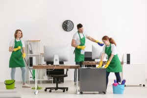 three people cleaning an office