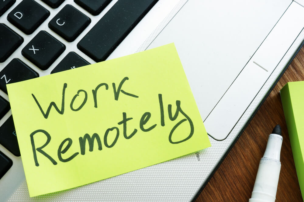 work remotely on a post it note that is on a laptop